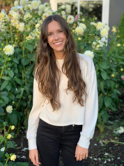 Picture of SMEA student Brittany Hoedemaker wearing a white shirt and black pants standing in front of green shrubs with yellow flowers