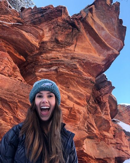 SMEA Student Brittany Hoedemaker wearing a blue down jacket and winter hat standing in front of a large, red rock formation in Sedona, AZ.