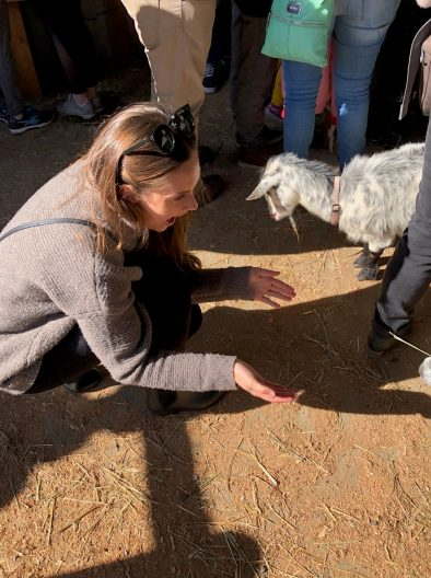 SMEA student Brittany Hoedemaker crouching down with outstretched arms greeting a small, white goat.