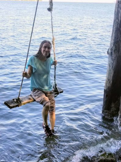 SMEA student Stephanie Wolek sits on a wooden swing suspended over water. She hangs onto the ropes holding the swing and has her legs and feet dangling down to and into the water.