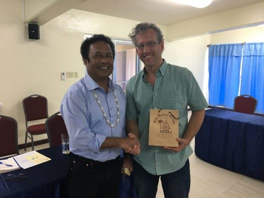 SMEA faculty member Patrick Christie, wearing a green, short-sleeved, button up shirt, holding a wooden plaque shakes hands with Palau's President, Thomas Remengesau Jr.