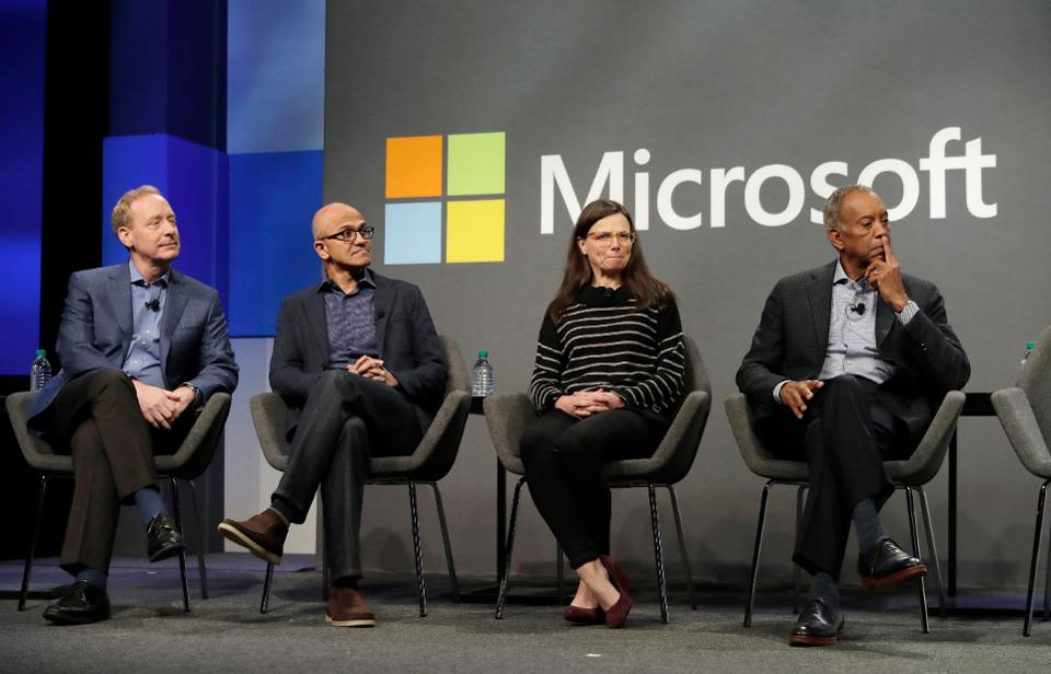 Four adult humans sit on a stage dressed in business attire in front of a Microsoft backdrop.
