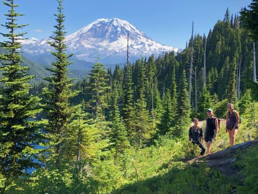 3 hikers standing in a clearing with evergreen trees on all sides of them. A snow-capped Mt. Rainier is in the distance.
