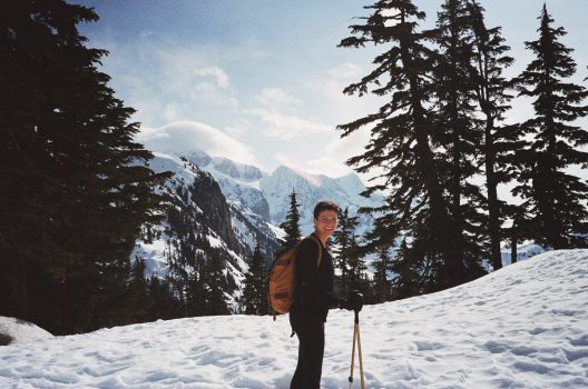 A woman wearing a backpack and carrying poles stands on a snow covered trail with trees and mountain tops visible in the background.