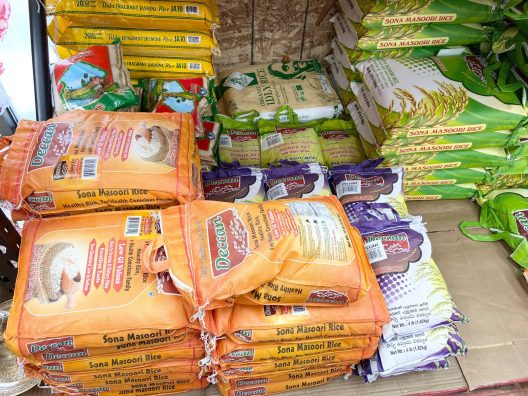 Various colorful bags of rice in a store stockroom