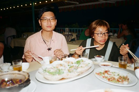 Two people seated at a table with chopsticks in their hands. On the table in front of them are various bowls of food, some containing cooked white rice.