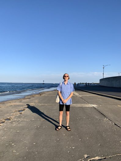 SMEA student Chris Boylan wearing a blue button up shirt, black shorts, sandals, and carrying a canvas bag over his shoulder stands on a walkway near a large body of water.