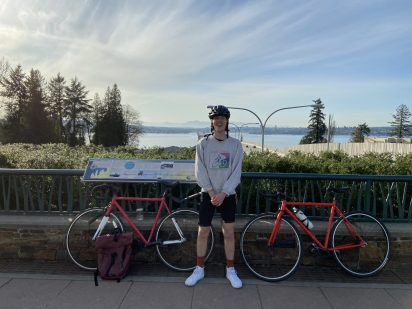 SMEA student Chris Boylan stands in a gray sweatshirt and black biking shorts wearing a bike helmet. He stands in front of an interpretive sign with two red bicycles, one on either side of him. There's a body of water in the distance.