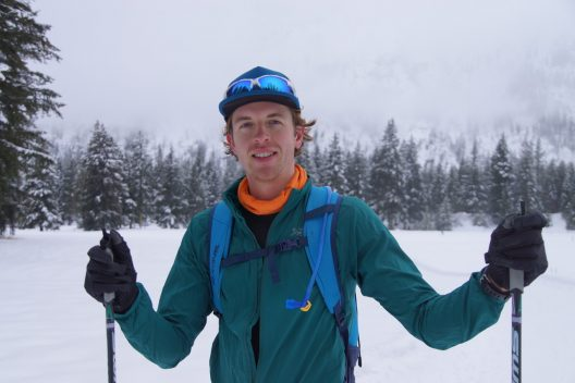 A white, adult man is wearing a green jacket, orange turtle neck, a blue backpack, black hat with sunglasses propped on the brim, and is holding ski poles in each hand. He's shown from the waist up standing on snow with trees in the background.