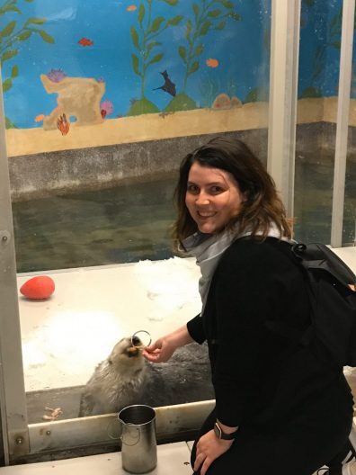 A young woman wearing a black jacket is petting the back of a gray sea otter. They appear to be in an aquarium enclosure.