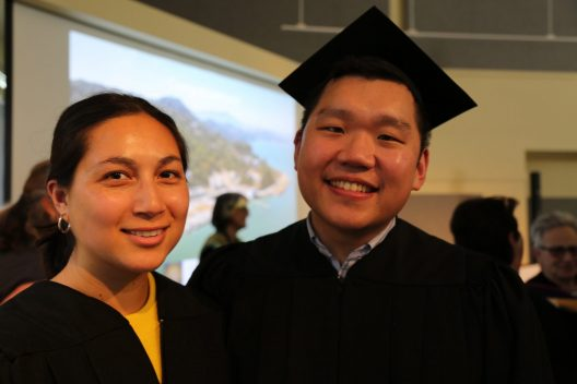 Two young people, one wearing graduation regalia including a mortarboard are seen standing in front of a large projection screen.