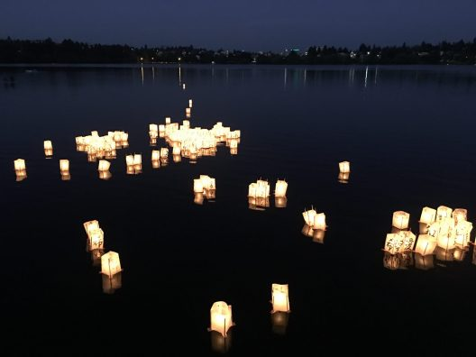 Floating lumnarias are seen at dusk floating on a calm water body. A shoreline spotted with lights is seen in the distance.