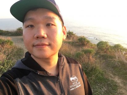SMEA student James Lee is shown with golden sunlight on half of his face and shoulders. He's wearing a black zip up hoodie and baseball cap.