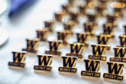 """A grid of metal pins with the University of Washington """"W"""" logo and the words """"Husky 100""""."""