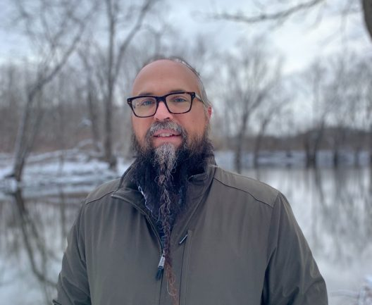 A man with a long, graying beard wearing glasses stands in front of a water body with snow covered ground and trees in the background.