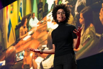 A black woman dressed in black, wearing glasses, and a microphone over her ear is speaking in front of a large theater screen. The picture displayed on the screen is a group of people meeting around a conference room table.