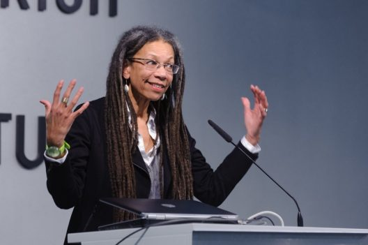 A black woman with long dreadlocks and glasses in a business suit stands at a podium with her arms held in the air mid-speech.